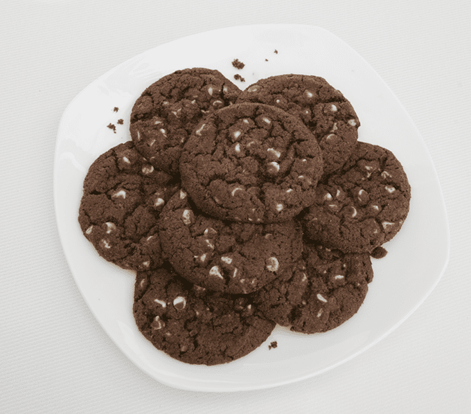 nicely arranged Chocolate Cookies with white chocolate chips on a white plate.