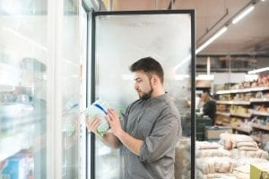 Man chooses frozen food in a supermarket fridge.
