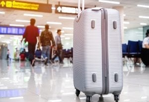 Suitcases at airport departure lounge traveler in airplane terminal background,traveling baggage in waiting area, focus on suitcase.