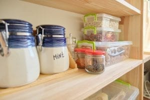Wooden shelves with food and kitchen utensils in the pantry.