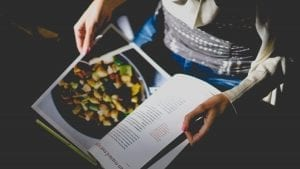 A person holding open a cookbook.